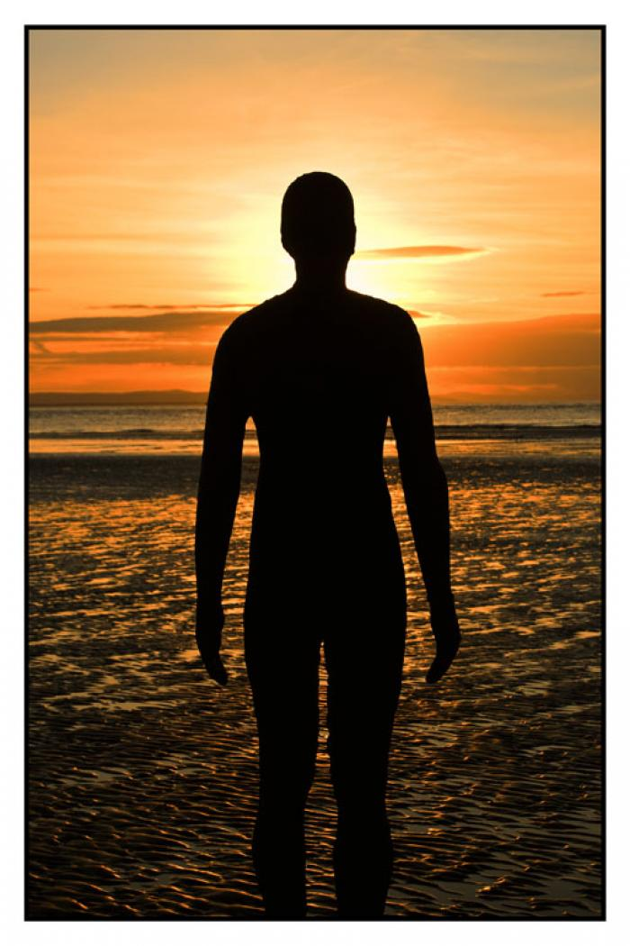 Statue silhouetted against the setting sun, Another Place, Crosby Beach